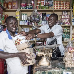 photo: Sven Torfinn. Uganda, Fort Portal, Rwenzori province, July 2015. Fort Portal, a fast expanding town in the foothills of the Rwenzori mountains. The urbanization attracts more people and creates non-agricultural economic activities. Farmers living around the town are providing food, especially for the low income settlers. Agricultural produce, fruits and vegetables, but also Matoke, or cooking plantain, or bananas, the staple food for most people in Uganda, is brought to town and sold on the markets. After sunset along the roads people set up stalls and sell a variety of food, fries, goats meat, chapatis, stew, Matoke. The informal street vendors provide food for the low-income settlers and people passing the town with public transport. A day in the life of a street food vender: Chris Byamukama, also known as: Black, 27 years. Chris is married to Rose Biira, 24 yrs, and they have 4 children together. He is the chairman of the Fort Portal food vendors Association. Chris is also training as a crime preventer together with 80 other youth from Fort Portal Municipality. Crime prevention a government program that aims at empowering the youth to keep law and order in their communities.  Chris prepares chapatis and sells them to people along the road. He starts in the afternoon, around 4pm, till 10pm in the night. With the profit he can sustain his family. The flour and cooking oil he buys in the store next door.